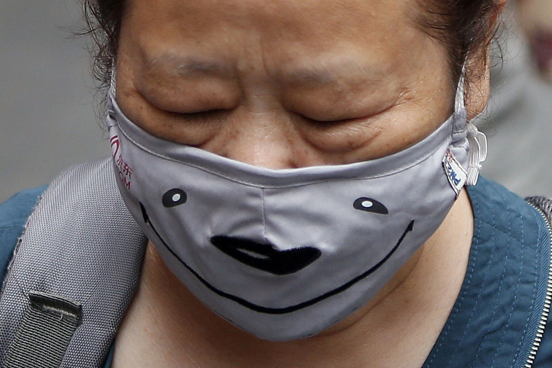 Žmonės Seulo gatvėse MERS saugosi žaismingomis kaukėmis.<br>Reuters/Scanpix nuotr.