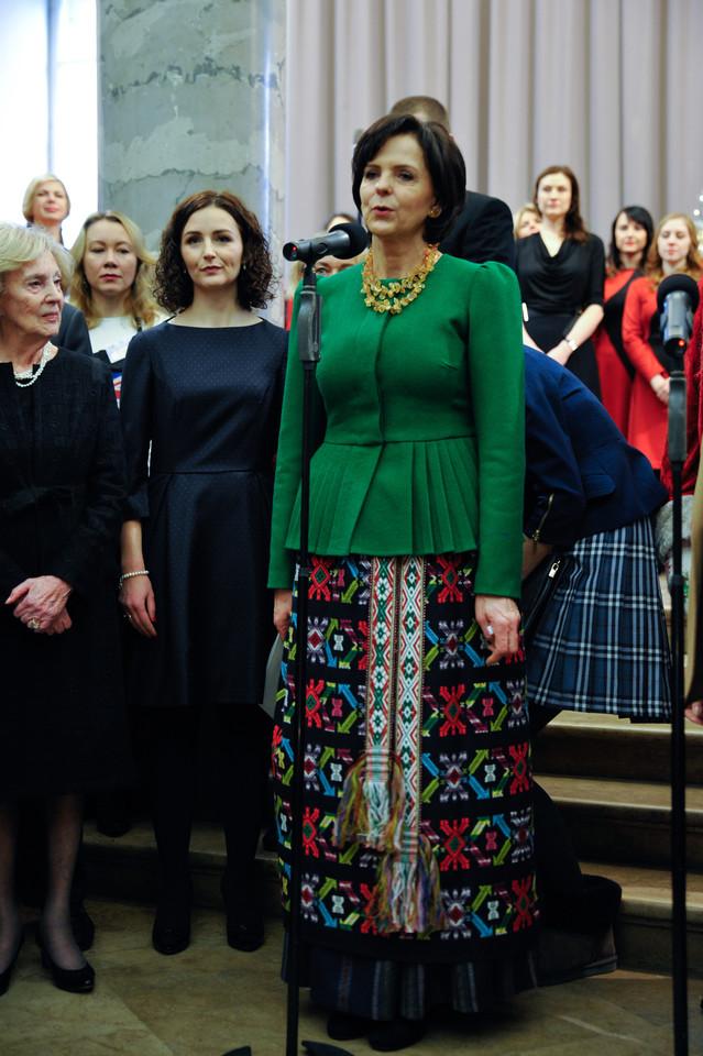 Ponia Janina sau parinko žalios spalvos švarką ir tautiniais raštais margintą sijoną, sujuostą tautine juosta, o kaklą papuošė gintariniais karoliais.
