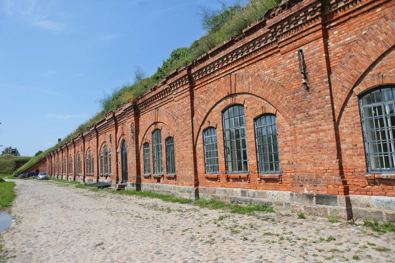 Raudonų plytų statiniai yra pasislėpė tarp žole apaugusių apkasų.<br>G.Bitvinsko nuotr.