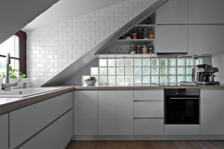 Siekiant tamsiam palėpiniam butui suteikti daugiau šviesos architektė nusprendė vonios kambarį įrengti už virtuvės erdvės, o bendroje šių kambarių sienoje pritaikyti stiklinius blokelius.<br>L.Garbačausko nuotr.