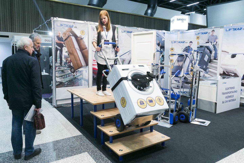 Ši mergina demonstravo įrangą, leidžiančią lengvai laiptais užgabenti net skalbimo mašiną.<br>T.Bauro nuotr.