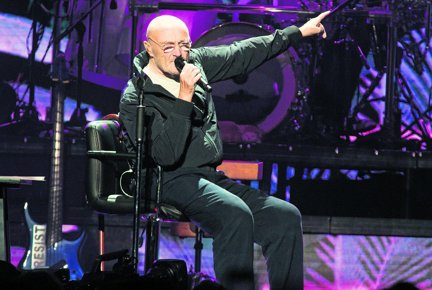 Ph.Collinsas į sceną žengia pasiramsčiuodamas lazdele ir visą koncertą yra priverstas sėdėti ant kėdės.<br>AP nuotr.