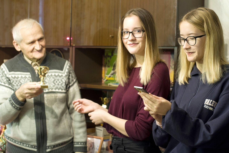 Jonas Patackas su anūkėmis Migle ir Aušrine susikalba žinutėmis.<br>Nijolės Zenkevičiūtės nuotr.