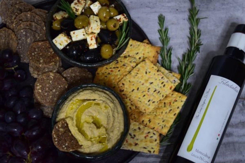 """Sveikų užkandžių rinkinys: avinžirnių humusas su krekeriais ir alyvuogių užkandėlė.<br>Nuotr. iš """"Skaniai sveikai""""."""