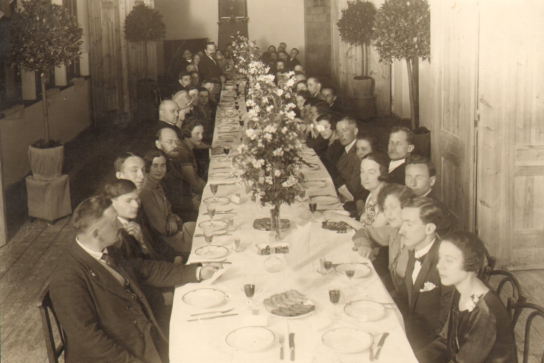 Kauno rusų gimnazijos dėstytojai ir svečiai prie šventinio stalo, padengto balta staltiese ir papuošto jazminų puokštėmis, 1935 m.<br>Lietuvos švietimo istorijos muziejaus nuotr.
