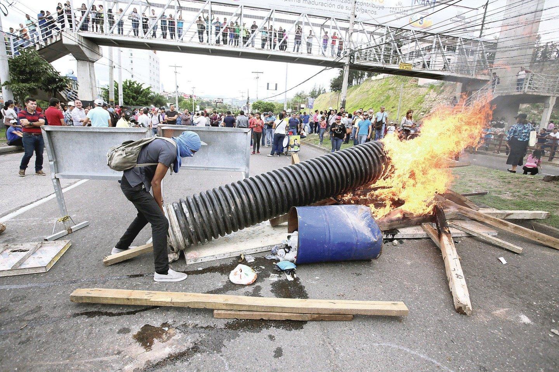 """Riaušės Hondūre – įprastas reiškinys. Žmonėms įgrisusi nelygybė, korupcija ir beviltiška situacija, iš kurios daugybė hondūriečių neišsikapsto visą gyvenimą.<br>""""Reuters""""/""""Scanpix"""" nuotr."""