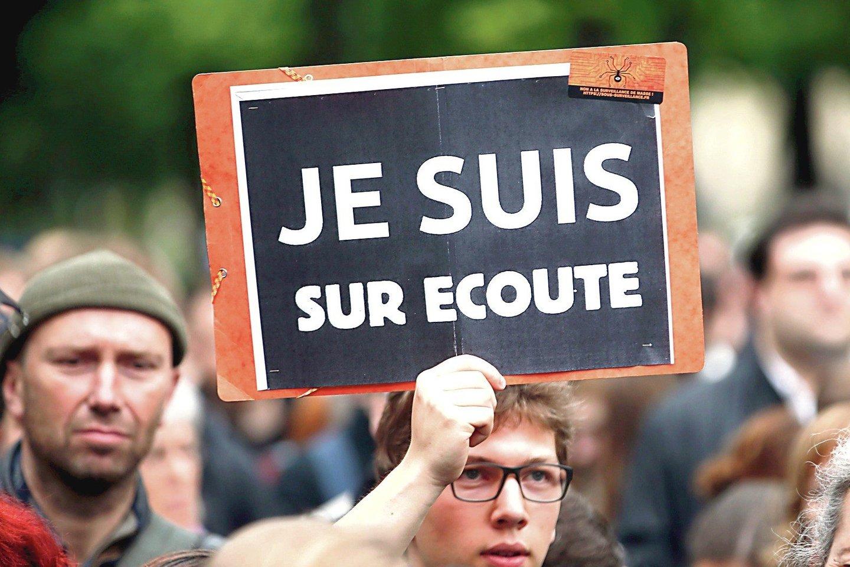 """Dar po sausio mėnesio išpuolių Paryžiuje, prie """"Charlie Hebdo"""" redakcijos, milijonai prancūzų nešė plakatus su užrašais """"Je suis Charlie"""" (""""Aš esu Charlie""""). Bet dabar pareigūnams užsimojus sekti Prancūzijos gyventojus jau pasirodė nauji plakatai """"Je suis sur ecoute"""" (""""Aš žinau, kad jie manęs klausosi"""").<br>AFP nuotr."""