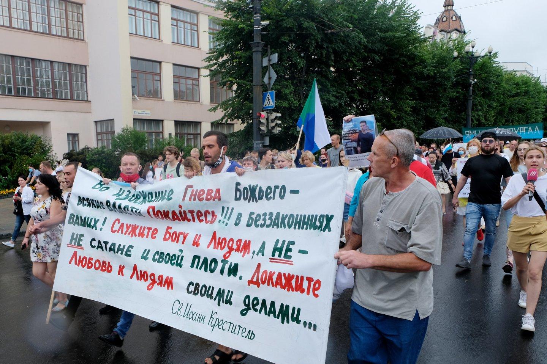 Rusijos Tolimųjų Rytų mieste Chabarovske tūkstančiai žmonių šeštadienį nepabūgo lietaus ir susirinko į naujas dideles protesto eitynes, reikšdami pasipiktinimą šio regiono populiaraus gubernatoriaus arešto.<br>TASS/Scanpix nuotr.