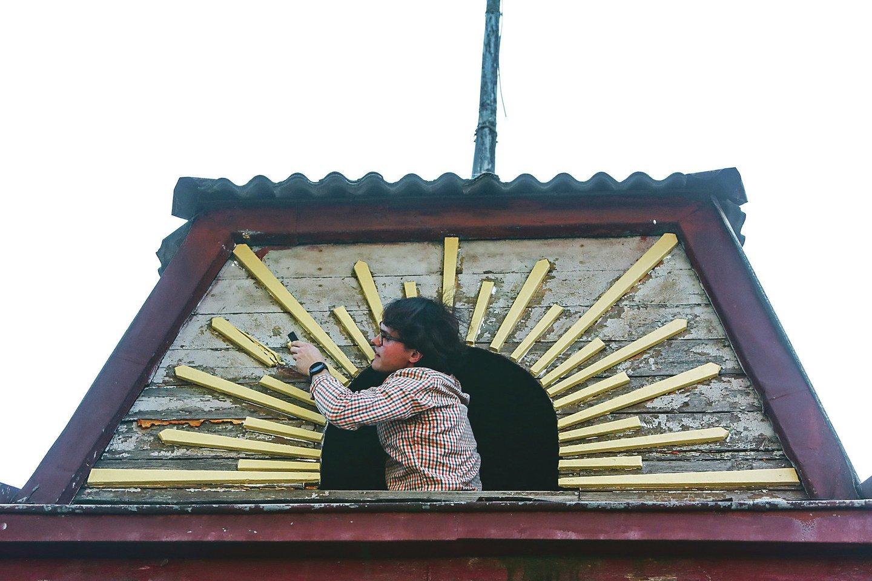 Kauno kolegijos studentai nušveitė medinius saulės spindulius ir juos perdažė. Šioms medinėms detalėms jau 90 metų.