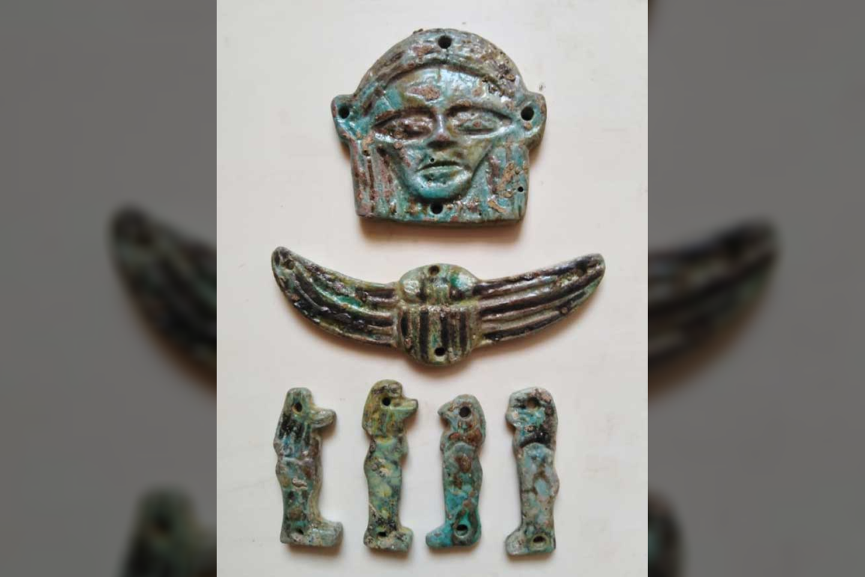 """Kai kurie amuletai vaizduoja deivės Hathor galvą, keturis dievo Horo sūnus, o taip pat rastas ir vienas sparnuotas amuletas.<br>""""Ahram Online"""" nuotr."""