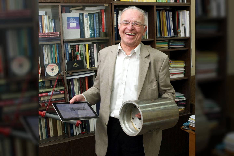 Prof. L. Telksnys 2011 m. Dešinėje profesoriaus rankoje - kelis šimtus gramų sverianti šiuolaikinė planšetė. Kairėje - 5kg sveriantis cilindras senovinio kompiuterio (16 MB) atminties.<br> R. Danisevičiaus nuotr.