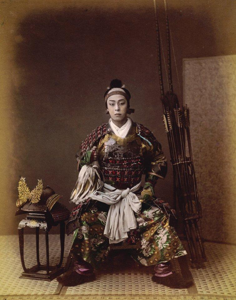 Kelias pirmąsias samurajų fotografijas padarė Felice Beato. Šiame ranka spalvintame 1867 metų portrete japonų karys sėdi šalia aukšto lanko ir strėlių ryšulio.<br>Leidėjų nuotr.