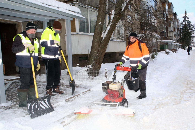 I.Kamarauskas daugiabučių prieigas valo motorizuotu šepečiu. Vyras uždirba daugiau nei sniegą kastuvais valantys kolegos.<br>M.Patašiaus nuotr.