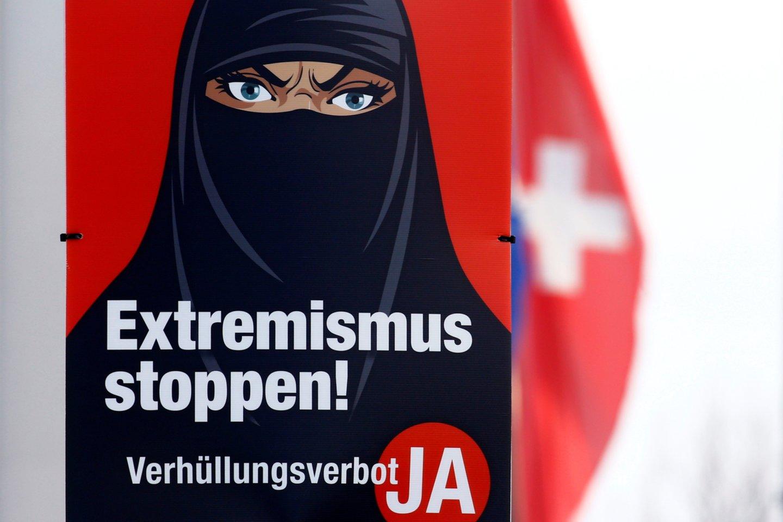 """Įvairiuose Šveicarijos miestuose buvo matyti kampanijos plakatų su užrašais """"Sustabdykime radikalų islamą!"""" ir """"Sustabdykime ekstremizmą!"""", kuriuose pavaizduota moteris, vilkinti juodą nikabą.<br>REUTERS/Scanpix nuotr."""