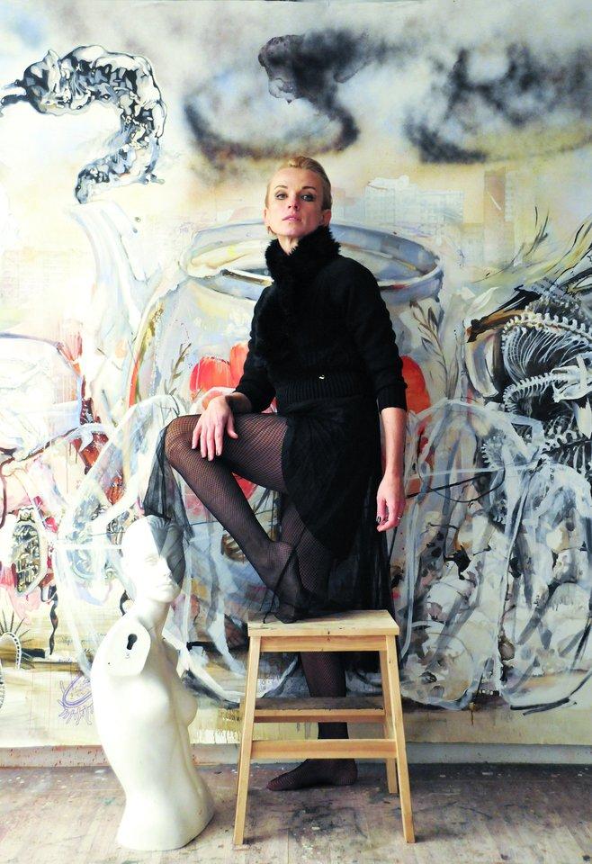 """M.Furmana pozavo studijoje prie paveikslo """"Kaip mama išsiuvinėjo sparnus ant mano nugaros"""".<br>Nuotr. iš asmeninio albumo"""