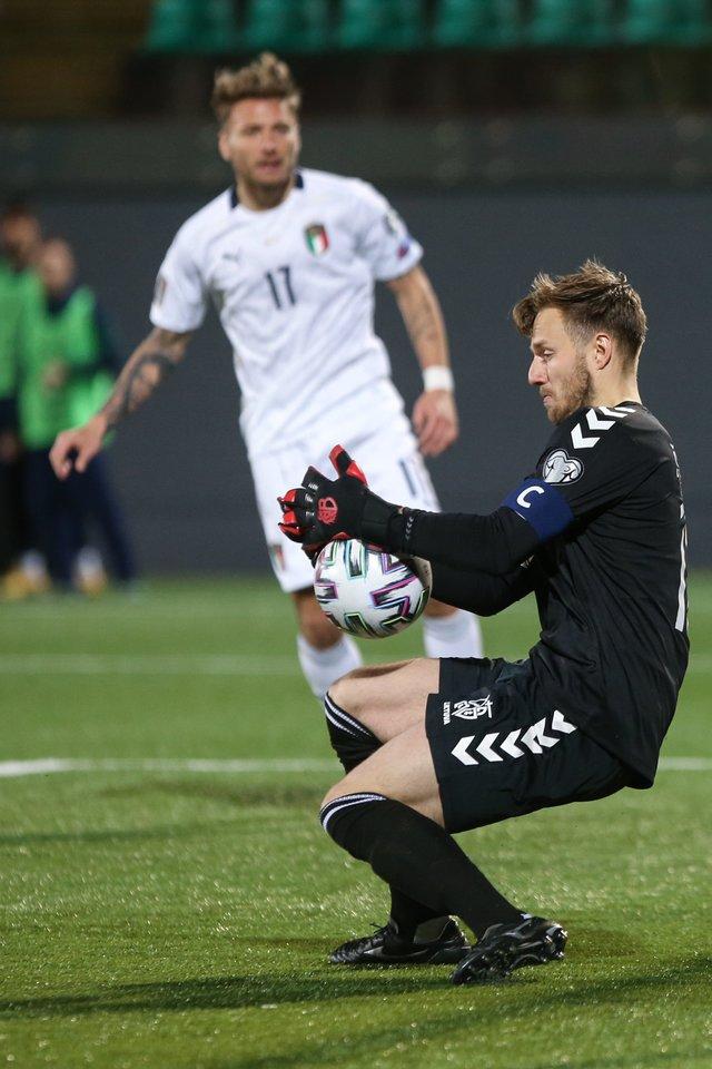 """""""Lazio"""" puolėjas C.Immobile stebi, kaip T.Švedkauskas tremia smūgį per Lietuvos ir Italijos rinktinių dvikovą.<br>R.Danisevičiaus nuotr."""