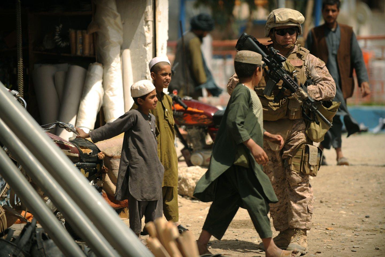 Amerikiečių karys eina pro vietinius vaikus Musa Kaloje.<br>AFP/Scanpix nuotr.