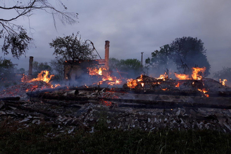 Iš nelaimės vietos nuotraukų matyti nuolaužas tikrinantys ugniagesiai. Iš namo beliko vos kelios nesudegusios sienos.<br>PAGD asociatyvi nuotr.