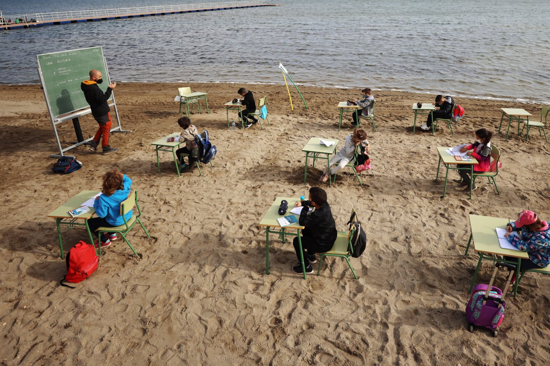 Mokytojai į paplūdimį atneša nešiojamą lentą ir suolus.<br>Scanpix / Reuters nuotr.
