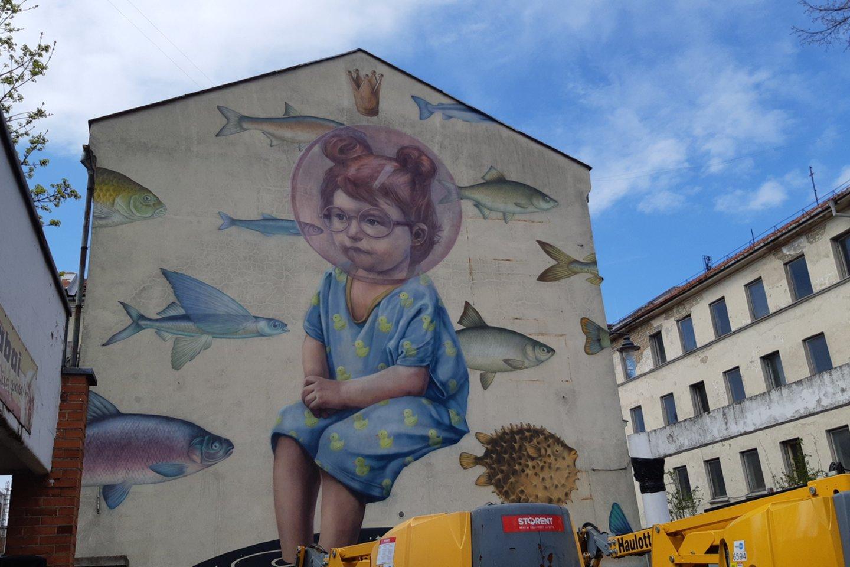 Mergaitė su žuvimis įsikūrė ant pastato J.Janonio gatvėje sienos.<br>A.Pilaitienės nuotr.