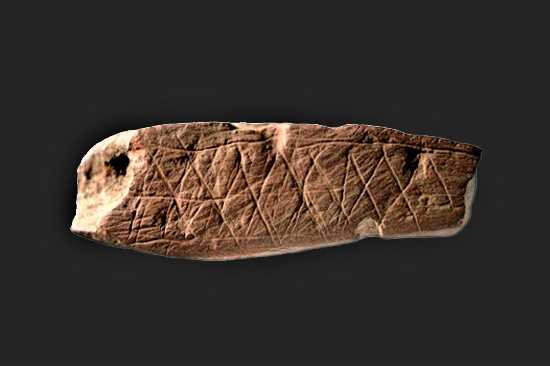 Nedidelis akmuo su aiškiais, tikslingai padarytais piešiniais, rastas Blombos oloje Pietų Afrikoje, laikomas pirmuoju įtikimu simbolinio mąstymo naudojimo žmonių bendravimui įrodymu. Šiam artefaktui maždaug 100 000 metų.<br>Wikimedia Commons