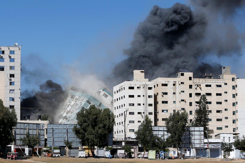 Vienas AP žurnalistas kiek anksčiau per tviterį parašė, kad Izraelio kariškiai prieš smūgį perspėjo pastato savininką apie būsimą ataką.<br>Reuters/Scanpix nuotr.