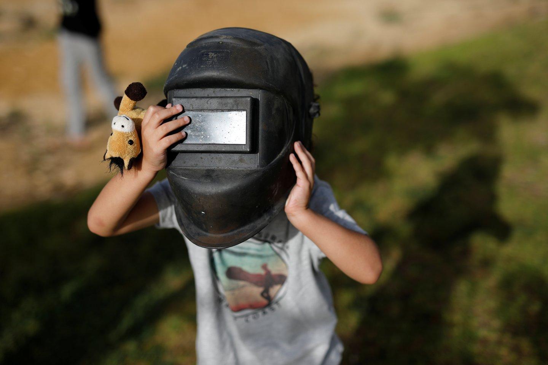 Vienas iš buitinių būdų stebėti Saulės užtemimą - pasitelkiant suvirintojo kaukę ar jos stiklelį.<br>Reuters / Scanpix nuotr.