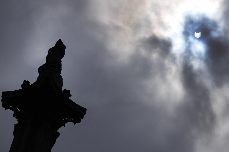 Dalinis Saulės užtemimas Trafalgaro aikštėje Londone.<br>AP / Scanpix nuotr.