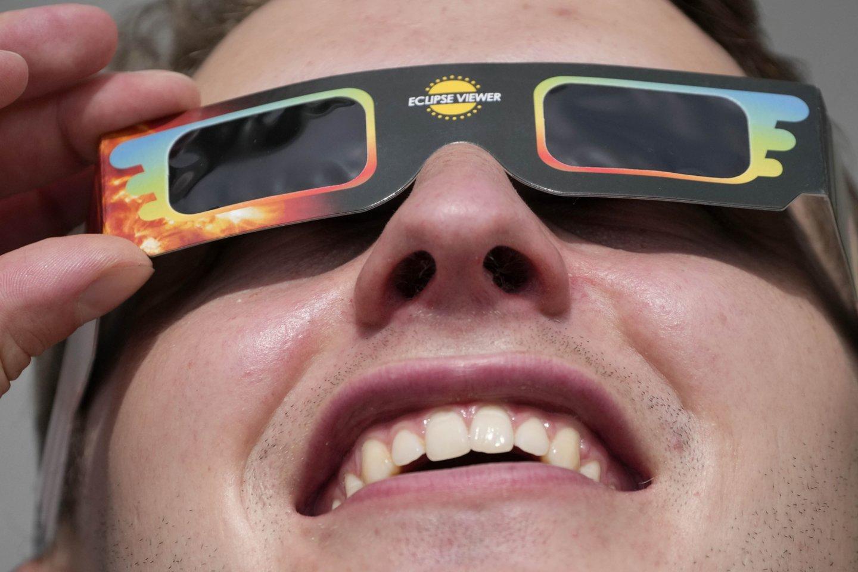 Saulės užtemimo stebėjimas Londone.<br>AP / Scanpix.