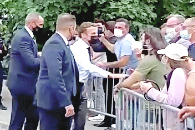 """Kai E.Macronas priėjo prie atitvarų ir sveikinosi su žmonėmis, vienas jų, užuot paspaudęs ištiestą ranką, jam sudavė.<br>""""Reuters""""/""""Scanpix"""" nuotr."""