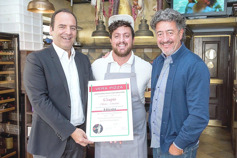 """2018 metais Italijos ir Lietuvos prekybos rūmų vadovas Ugo Meucci (kairėje) Užupio picerijos virtuvės vadovui F.Meschino (viduryje) įteikė """"Associazione Verace Pizza Napoletana"""" sertifikatą. Dešinėje – picerijos savininkas A.Meschino.<br>R.Danisevičiaus nuotr."""