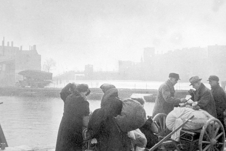 """Karaliaučiaus gyventojai sugriauto miesto gatvėse. Tolumoje matyti sovietų """"katiuša"""".<br>Leidėjų nuotr."""