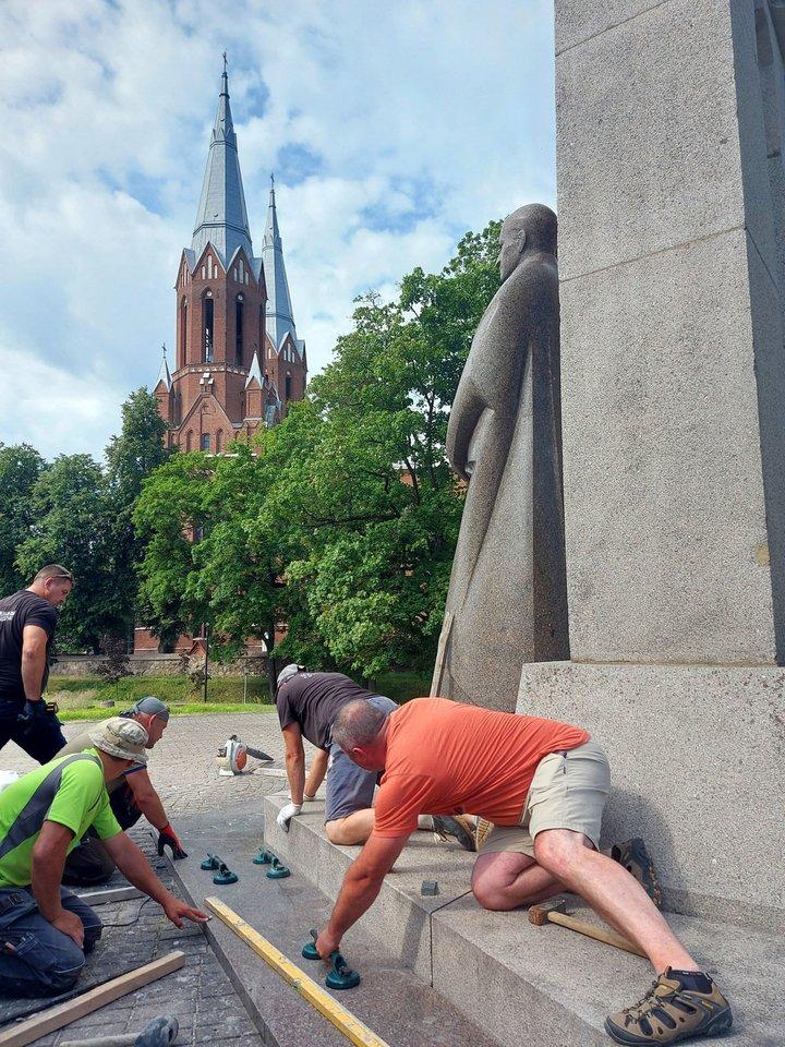 Skulptoriaus A.Sakalausko pagalbininkai sutvirtino paminklo postamentą juosiantį akmens plokščių žiedą.<br>T.Kontrimavičiaus nuotr.