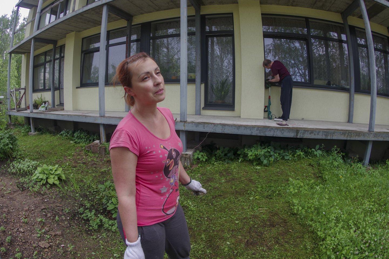 Pirmajame aukšte gyvenanti Liubovė bent po langais apsitvarko teritoriją.<br>V.Ščiavinsko nuotr.