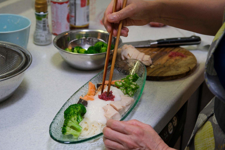 Nuotraukoje – šeimininkės Yoko Nishimura gamintas maistas. Y.Nishimura tapo viena iš konkurso nugalėtojų ir savo patiekalus pristatė olimpiniame kaimelyje.<br>AFP/Scanpix nuotr.