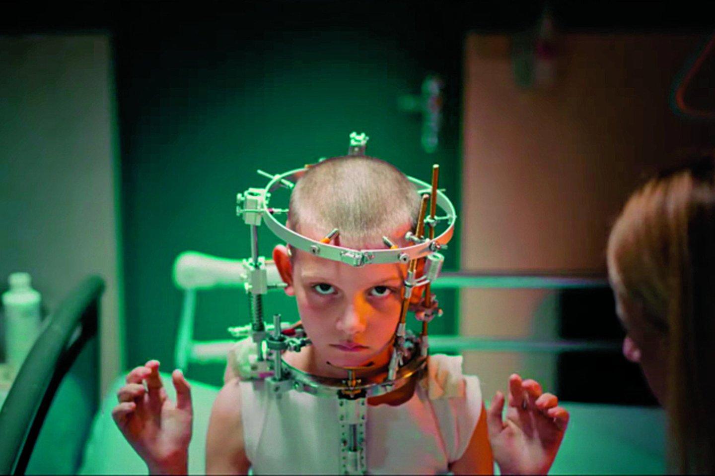 """Po avarijos nuskusta Aleksos galva įspraudžiama į geležinį vainiką su spygliais.<br>Kadras iš filmo """"Titanė"""""""