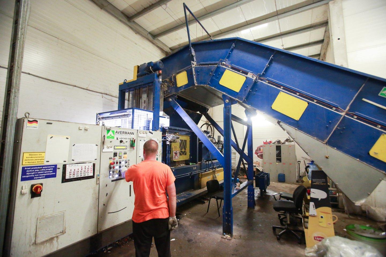 Galingas pramoninis presas suspaudžia parduotuvėse surinktas ir išrūšiuotas popieriaus bei plastiko pakuotes.