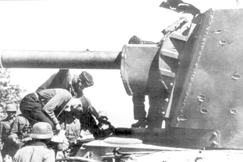 Vokiečiai prie pamušto KV-2. Ant tanko bokštelio matyti 37 cm pabūklo daugkartinių pataikymų žymės. 1941 m. birželio mėn., Lietuva.<br>Leidėjų nuotr.