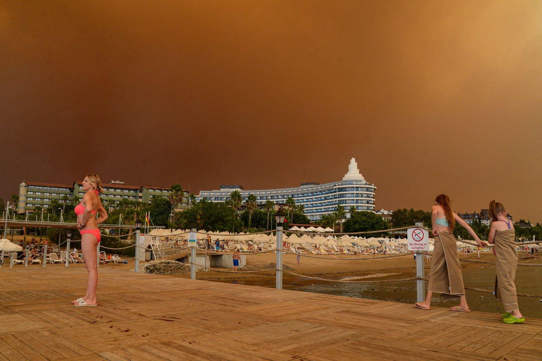 Manavgato mieste prie pajūrio viešbučių komplekso tiršti dūmai padangę nudažė tamsiai oranžine spalva.<br>AFP/Scanpix nuotr.