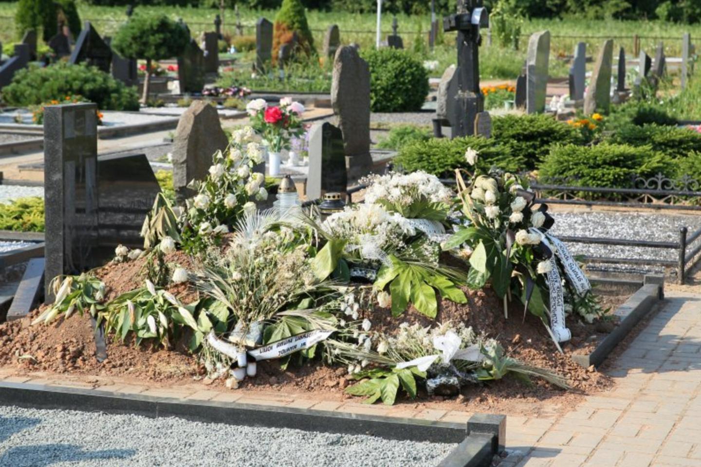 Naujamiesčio kapinėse laidodami senolę artimieji turėjo stebėti siaubingą vaizdą, kaip duobkasiai iš per mažos duobės krapšto įstrigusį karstą su palaikais.<br>A.Švelnos nuotr.