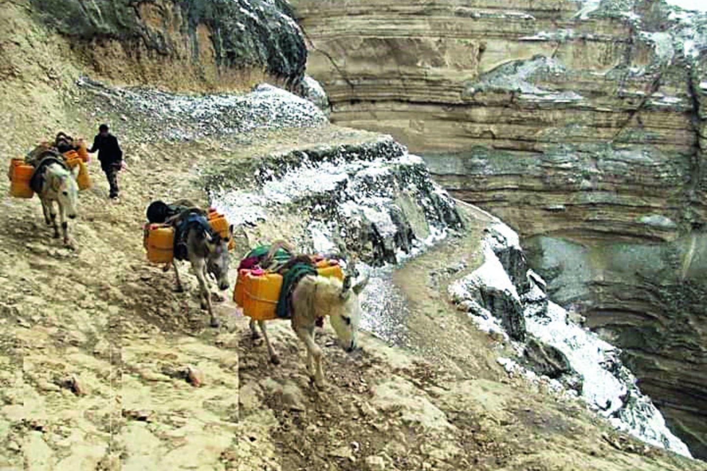 Vandenį į namus moterys neša per kalnus.