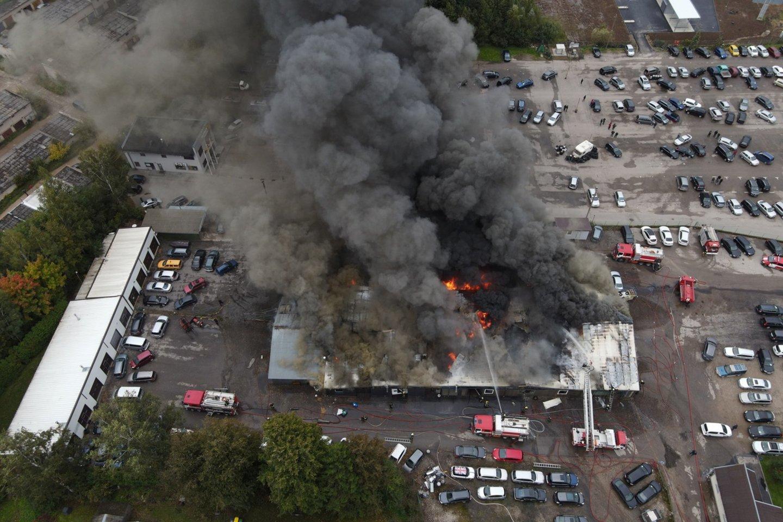 Utenos automobilių turguje užsiliepsnojus angarui į dangų pakilo tirštų juodų dūmų stulpas.<br>Marijaus Kaukėno nuotr.