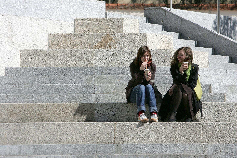 Ant laiptų sėdinčios merginos geria kavą. Jaunimas, poilsis, džiaugsmas, laimė, draugystė, moterys<br>V.Balkūno nuotr.