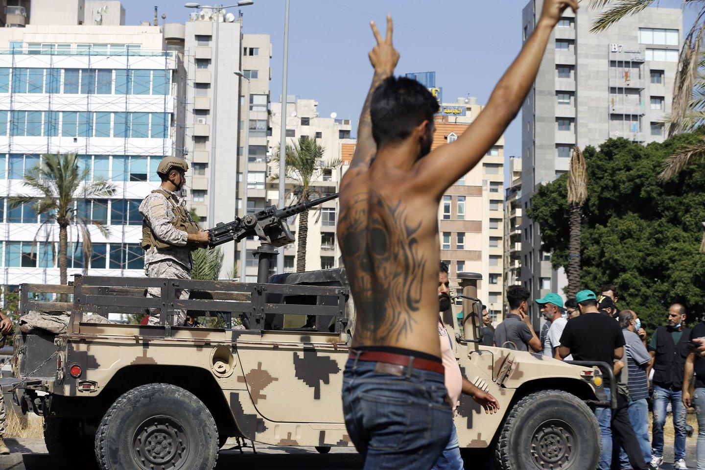 Visuomeninės televizijos reportažuose matyti, kaip ginkluoti vyrai neša šautuvus ir sunkiąją ginkluotę.<br>AP/Scanpix nuotr.